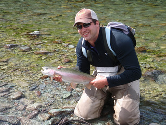 Fly Fisherman kneels in pristine waters holding trout