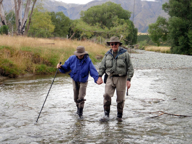 Couple enjoying a walk in the river while on a fly fishing trip